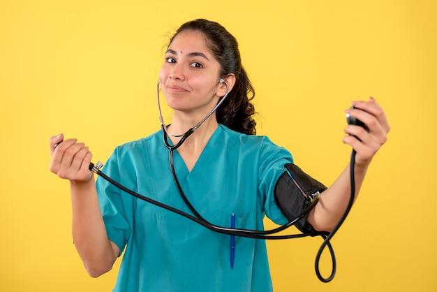 黄色の背景に立っている血圧計を保持している制服を着た幸せな女性医師の正面図