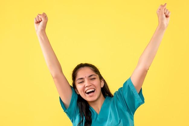 노란색 격리 된 배경에 그녀의 행복을 보여주는 제복을 입은 전면보기 행복 여성 의사