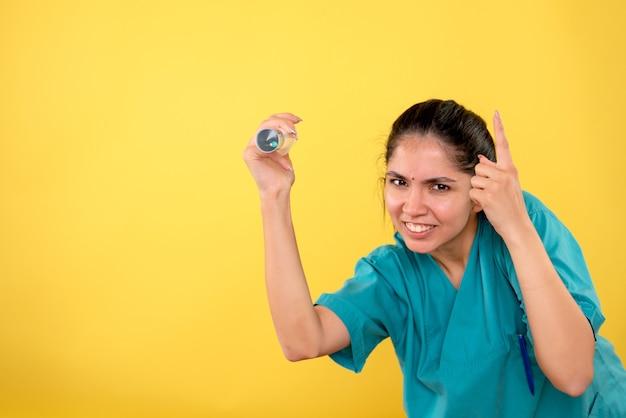 노란색 바탕에 주사기와 전면보기 행복 한 여성 의사
