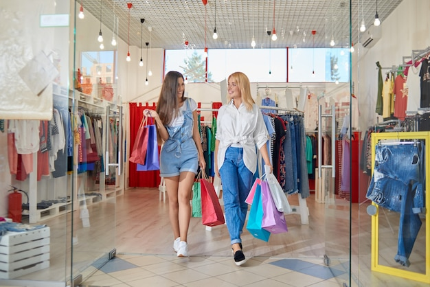 Front view of happy female friends coming out of clothing store