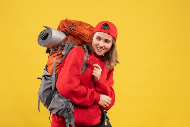 Вид спереди счастливая туристка с рюкзаком, держащим кредитную карту