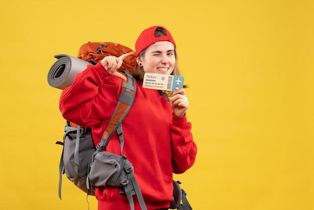 Вид спереди счастливая туристка с рюкзаком, держащим билет на самолет