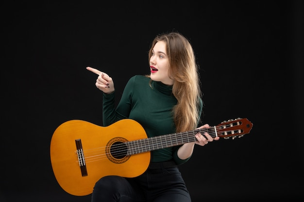 Front view of happy female musician holding guitar and pointing something on the right side on black