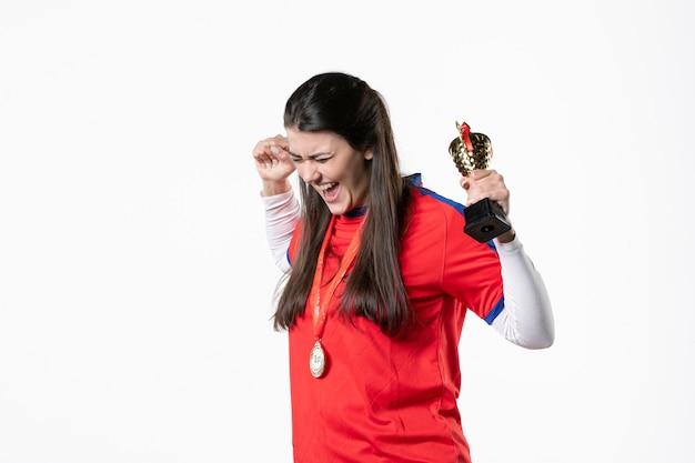 Вид спереди счастливая женщина-игрок в спортивной одежде с медалью и золотой чашей