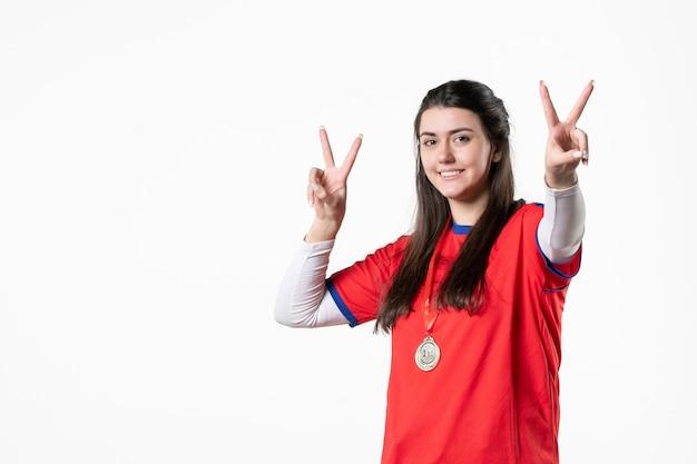 Вид спереди счастливая женщина-игрок в спортивной одежде с медалью