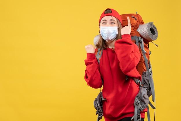 배낭과 마스크 천장에서 가리키는 전면보기 행복 여성 관광