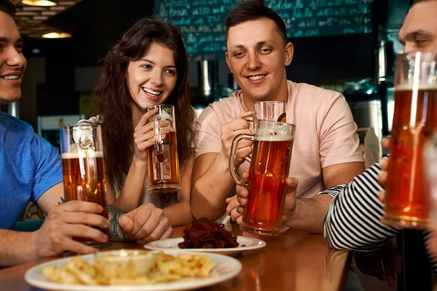 Front view of happy friends sitting together and drinking beer in cafe. pretty woman sitting in male company, eating snack, talking and laughing in pub. concept of leisure and fun.