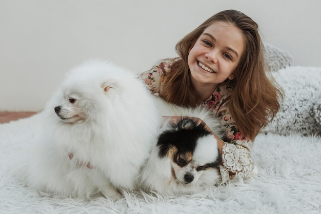 Front view happy girl and two fluffy dogs