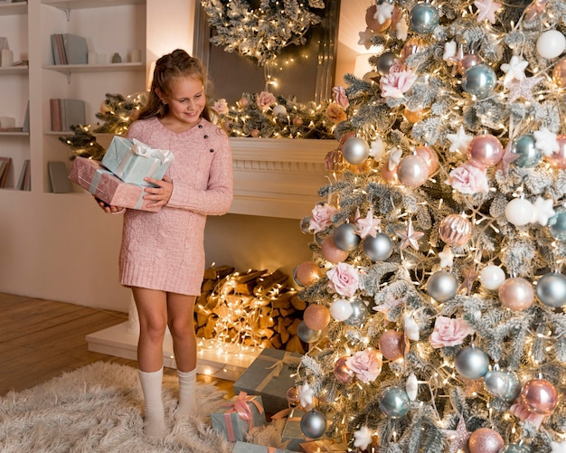 Front view of happy girl with gifts and christmas tree