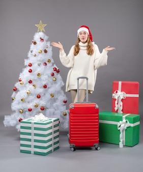 Вид спереди счастливая девушка в шляпе санта-клауса, открывая руки, стоя возле елки и подарков