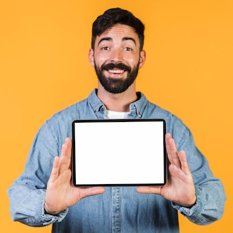Front view happy guy holding a tablet