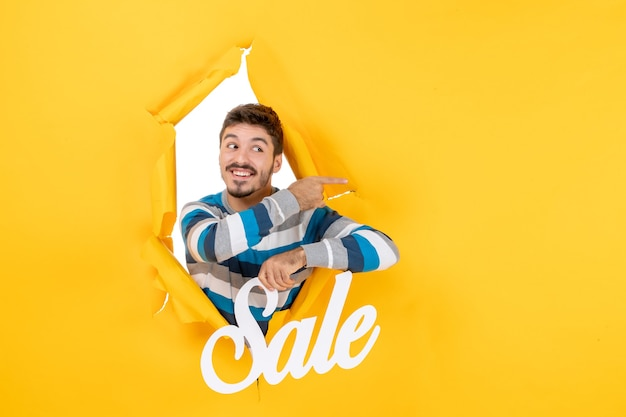 Front view happy handsome man holding up sale letters peeping through wall
