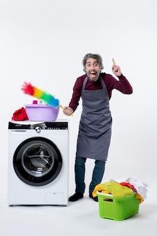 Vista frontale felice governante uomo che tiene spolverino in piedi vicino al cesto della biancheria della lavatrice su sfondo bianco
