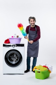 흰색 배경에 세탁기 근처에 서 있는 깃털 살포기를 들고 있는 행복한 가정부 남자