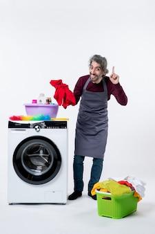 흰색 격리된 배경에 세탁기 근처에 서 있는 세탁물을 들고 있는 행복한 가정부 남자 전면 보기