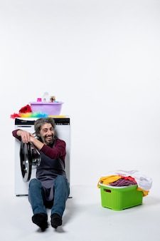 Front view happy housekeeper man sitting near laundry basket on white background