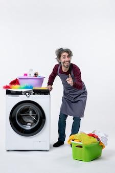 Вид спереди счастливый домработница, стоящая возле белой корзины для белья стиральной машины на полу