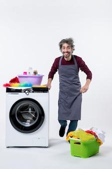 Uomo felice della governante di vista frontale che sta vicino alla lavatrice bianca su fondo bianco