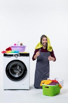 正面図白い背景の上の彼の頭の上の膝の洗濯物の上に立っている幸せな家政婦の男