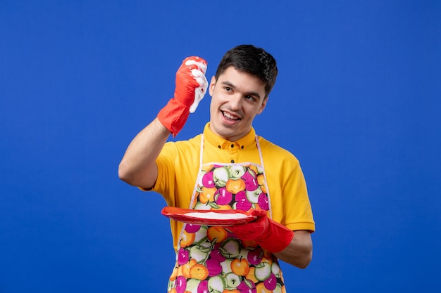 Vista frontale felice governante spremere la spugna per piatti su spazio blu