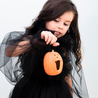 Front view happy little girl holding a pumpkin