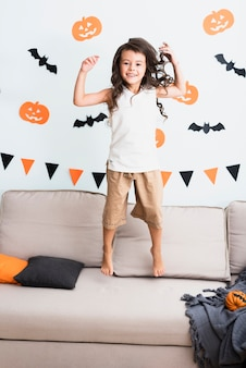 Front view happy little girl jumping on couch