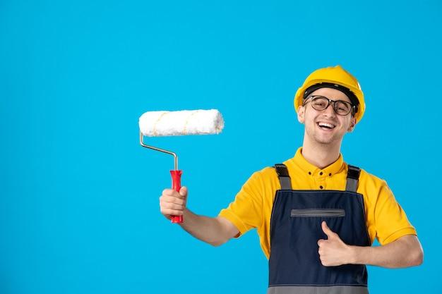 Vista frontale del costruttore maschio felice in uniforme con il rullo di vernice nelle sue mani sulla superficie blu