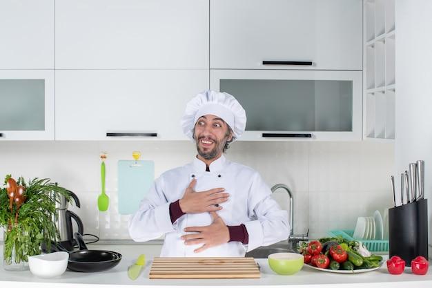 부엌 식탁 뒤에 서 있는 가슴에 손을 얹고 요리사 모자를 쓴 행복한 남성 요리사의 전면 모습