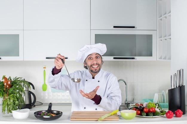현대 부엌에서 국자를 들고 제복을 입은 행복한 남성 요리사