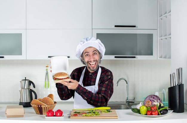 Front view happy male cook holding up burger in the kitchen