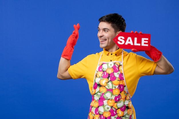 Governante maschio felice di vista frontale con i guanti rossi dello scolo che tengono il segno di vendita sullo spazio blu