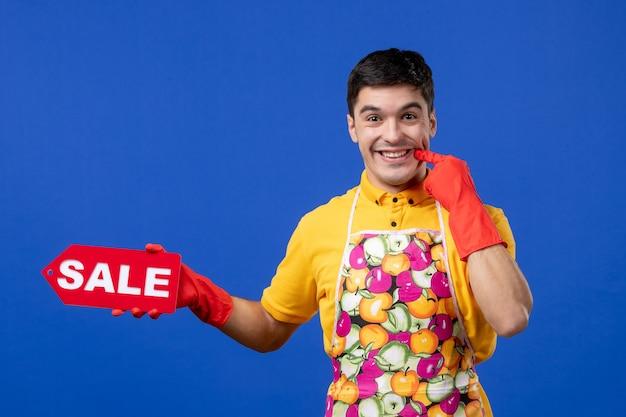 Vista frontale felice governante maschio in maglietta gialla con cartello di vendita che mostra il suo sorriso sullo spazio blu