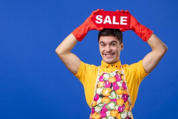 Vista frontale felice governante maschio in maglietta gialla che alza il cartello di vendita sopra la sua testa su spazio blu blue