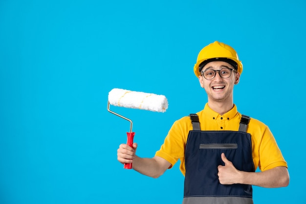 Front view of happy male worker in uniform and helmet with paint roller on a blue surface
