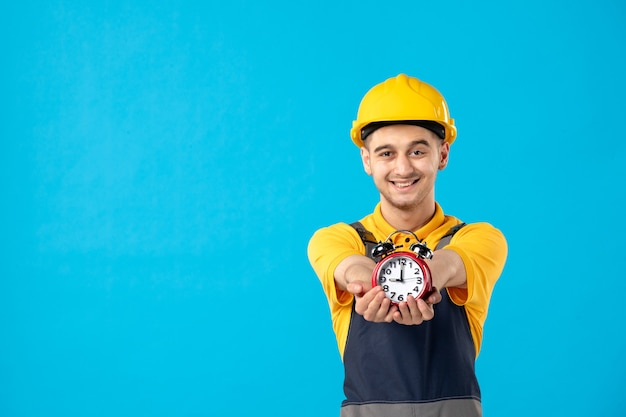 Front view of happy male worker in yellow uniform with clocks on blue wall