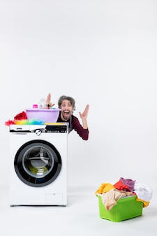Front view happy man in apron sitting behind washer laundry basket on white background