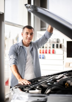 Uomo felice di vista frontale che controlla un'automobile