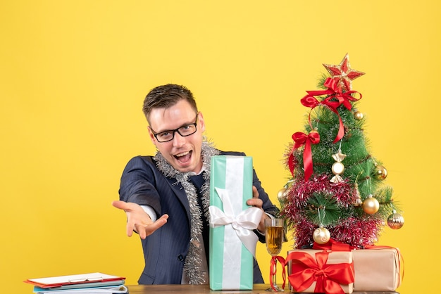Front view of happy man giving hand sitting at the table near xmas tree and presents on yellow