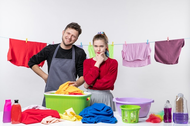 Front view of happy man and his wife putting her hand on her chin laundry baskets and cleaning stuffs on table on white wall