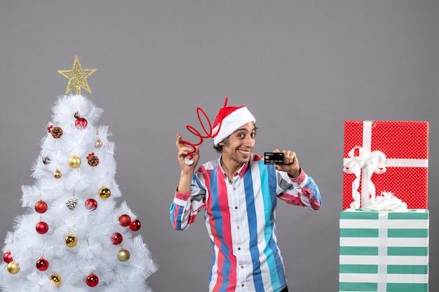 Вид спереди счастливый человек, держащий шляпу санта-клауса и кредитную карту, стоящий возле белой рождественской елки