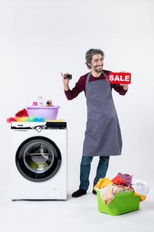 흰색 배경에 있는 세탁기 세탁 바구니 근처에 서 있는 카드와 판매 표지판을 들고 있는 행복한 남자