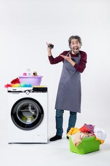 Vista frontale uomo felice che sostiene la carta in piedi vicino al cesto della biancheria della lavatrice su sfondo bianco white
