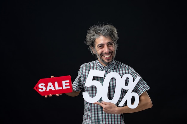 Front view of happy man holding up white mark and red sale sign on black wall