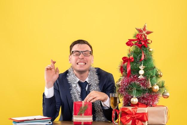 Vista frontale dell'uomo felice che fa segno di buona fortuna che si siede al tavolo vicino all'albero di natale e presenta su giallo