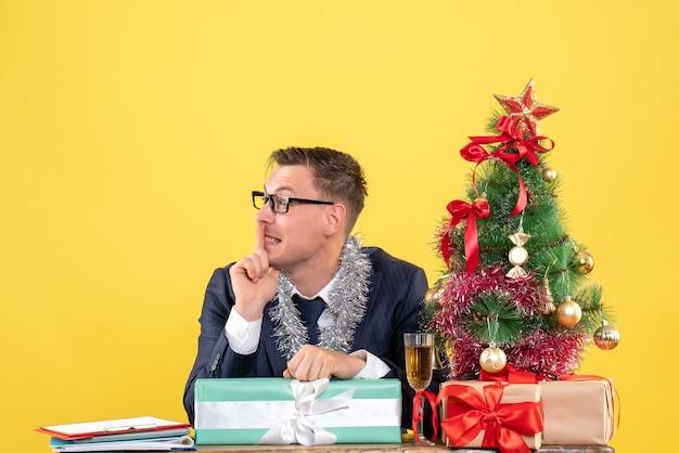 Vista frontale dell'uomo felice che fa segno di shh seduto al tavolo vicino all'albero di natale e regali su giallo