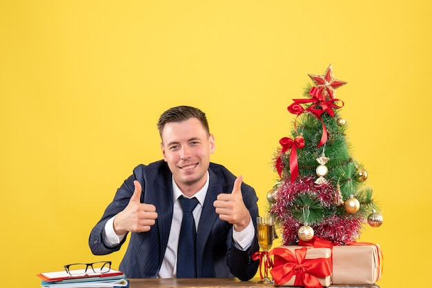 Front view of happy man making thumb up sign sitting at the table near xmas tree and gifts on yellow