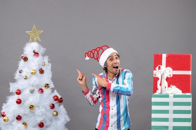 正面図幸せな男は白いクリスマスツリーの近くにクリスマスツリーを示す指を指さした
