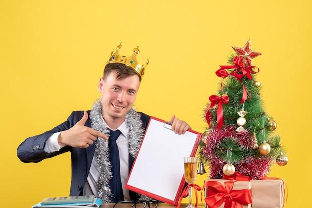 Vista frontale dell'uomo felice che indica alla lavagna per appunti che si siede al tavolo vicino all'albero di natale e presenta su colore giallo