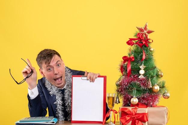 Vista frontale dell'uomo felice che si siede al tavolo vicino all'albero di natale e regali su giallo
