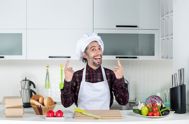 Front view happy man standing behind kitchen table in the kitchen